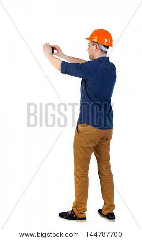 Backview of an engineer in construction helmet stands and using photo camera. Standing young guy. man in a blue shirt and helmet phone photographs.