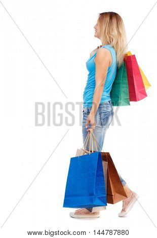 side view of going woman with shopping bags . beautiful girl in motion. Isolated over white background. The blonde in a blue t-shirt and jeans is going sideways to the camera with a paper shopping