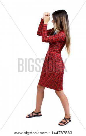 skinny woman funny fights waving his arms and legs. The girl in red plaid covers his face with his hands in a fighting stance.