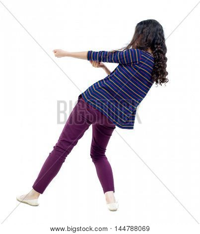 back view of standing girl pulling a rope from the top or cling to something. Long-haired curly girl in a striped blouse pulling a rope.