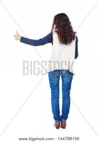 Back view of woman thumbs up. Long-haired girl with curly hair shows thumb up at arm's length.