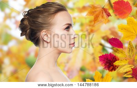 health, people, season and beauty concept - beautiful young woman face over autumn leaves background
