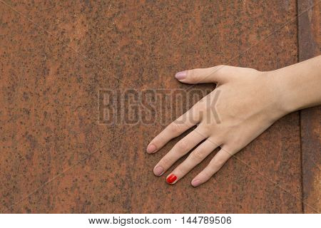 A Hand Touching Weathered Rusty Metal Texture