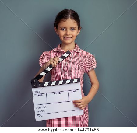 Charming little girl in cute dress is holding clappers looking at camera and smiling standing on gray background