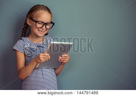Cute little girl in dress and eyeglasses is using a digital tablet and smiling standing on gray background