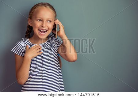 Cute little girl in dress is talking on the mobile phone and smiling standing on gray background