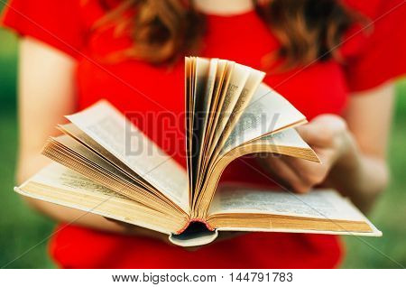 detail from a woman reading a book. Closeup of a woman holding a old book outdoors. woman holding a book behind a nature backgraund. Female hands holding an old book. woman reading a book