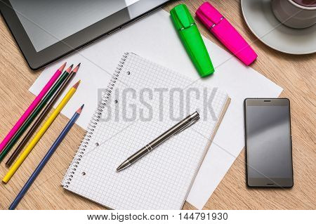 Notepad, Mobile Phone, Paper, Pencils And Tablet On Table