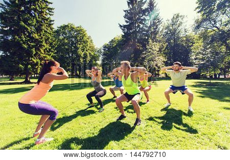 fitness, sport, friendship and healthy lifestyle concept - group of happy teenage friends exercising and doing squats at boot camp