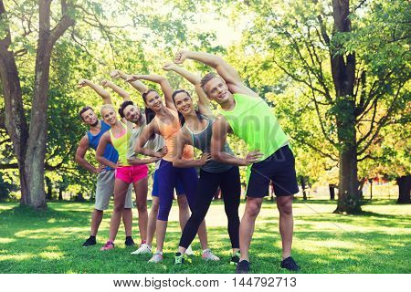 fitness, sport, friendship and healthy lifestyle concept - group of happy teenage friends or sportsmen exercising and stretching hands at boot camp