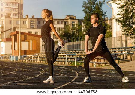 Young adults in sportswear doing warming up exercises outdoors. Fitness workout