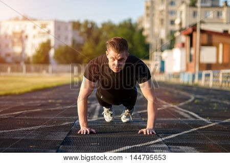 Young caucasian man doing press ups exercises, fitness workout outdoors