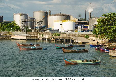 Photo of the Factory or plant near water with boats. Industrial district