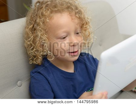 a little blond boy with a digital tablet