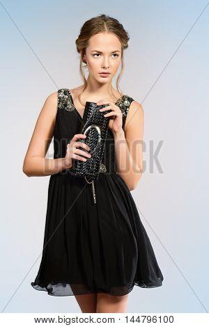 Pretty young woman in little black dress. Beauty, fashion. Studio shot.