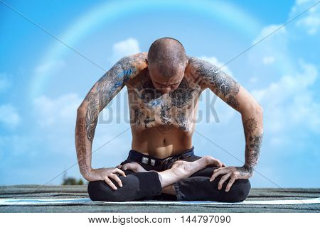 Yoga concept. Experienced yoga master meditates in the lotus position sitting on a roof over blue sky.