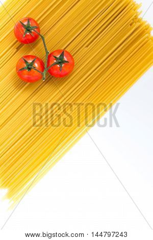 Uncooked spaghetti and cherry tomato on white background. Top view with copy space.