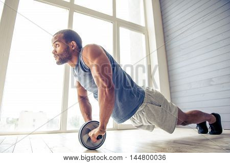 Handsome Afro American sportsman is doing ab wheel rollout exercise and looking forward while working out at home poster