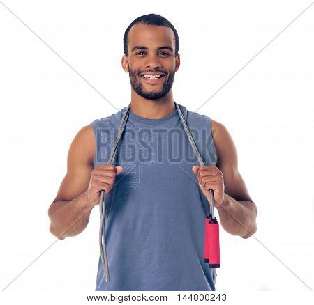 Handsome Afro American sportsman is holding a jumping rope looking at camera and smiling isolated on white background poster