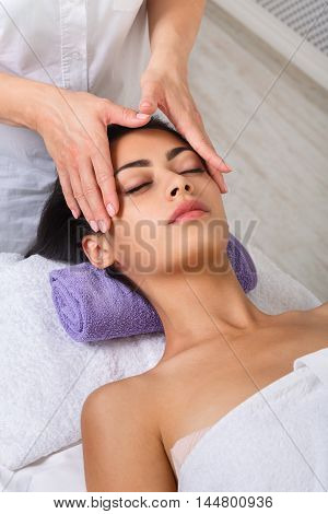 Head massage in spa. Female beautician doctor with patient in wellness center. Professional cosmetologist make procedure to beautiful indian girl in cosmetology cabinet or beauty parlor.