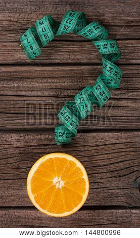 Question mark with orange fruit over wooden background