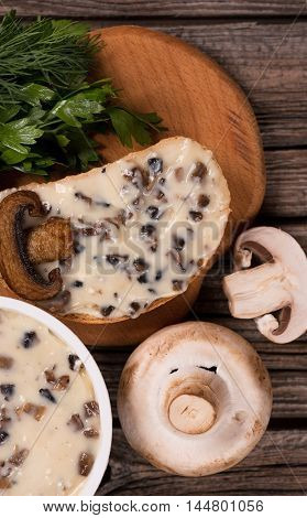 Tasty sandwich with processed mushrooms cheese on the wooden surface