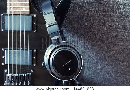 black electric guitar and headphones for music recording
