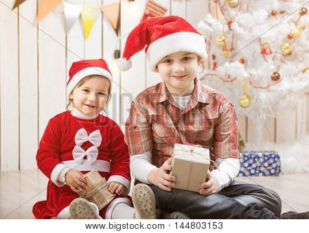Kids in red santa hats sitting in decorated room with present boxes in hands