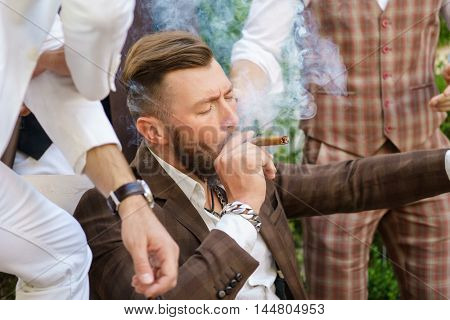 Handsome young guy with closed eyes enjoying cigar
