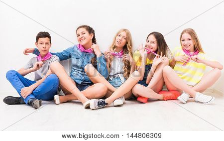 cute smiling tenagers sitting on the floor with legs crossed
