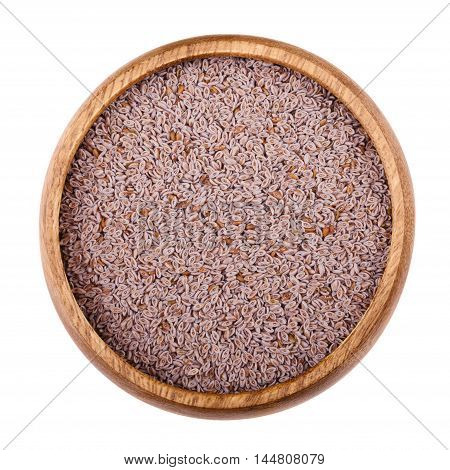 Psyllium seed husks in a wooden bowl on white background. Dried fruits, used in cooking  to produce an edible mucilage, a thick gluey substance. Also used as a dietary fiber. Isolated macro close up.