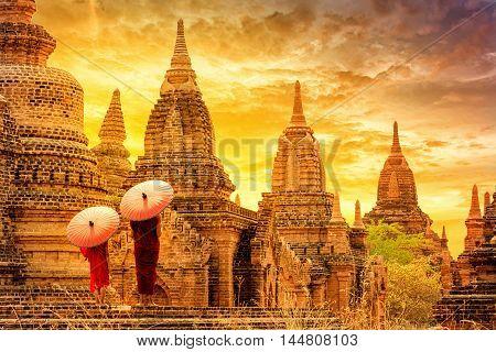 Novice monk with red umbrella walking around ba-gan Pagoda Ba gan Myanmar.