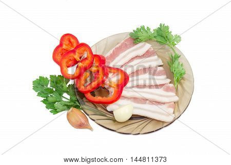 Uncooked slices of streaky pork belly bacon on glass saucer sliced bell pepper sprigs parsley and coriander garlic cloves on a light background
