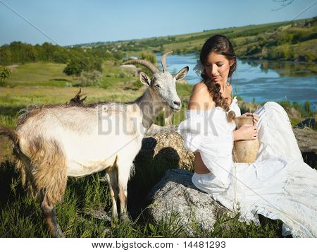 beautiful woman herding goats in nature, holding a pitcher of milk poster