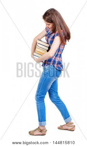 Girl carries a heavy pile of books. back view. Girl in plaid shirt trying more convenient to pick up a stack of books.
