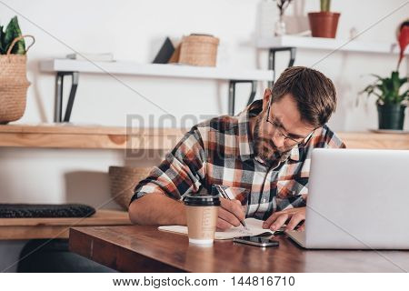 Focused young entrepreneur sitting at a table at home writing in a notebook next to a laptop