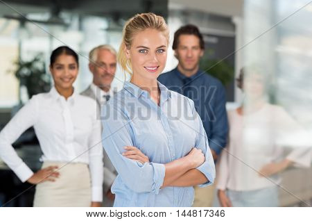 Portrait of a proud busineswoman looking at camera in a modern office. Successful happy woman standing with her staff in background. Beautiful young business woman smiling with colleagues in office.