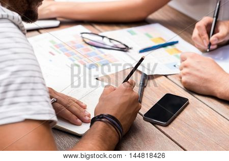 Students discussing the charts and graphs on wooden table. Close up of students hands writing on paper and notebook. Finance students analyzing report of company as assignment.