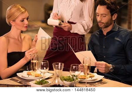 Cheerful couple with menu in a restaurant making order. Young waitress offering to young couple tasty dishes. Young couple ordering for dessert after dinner.