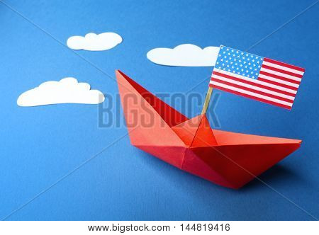 Paper boat with American flag on blue background. Happy Columbus day concept