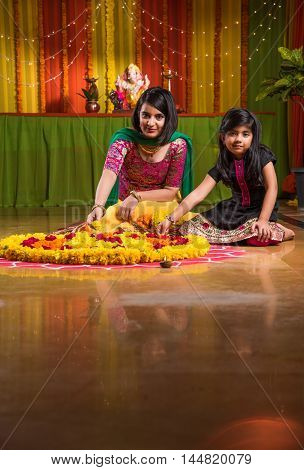 two Indian girls making rangoli using flower, asian girls making rangoli using flower