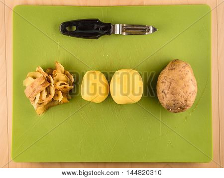Two unpeeled and one peeled potatoes with skins on green plastic board with peeler, simple food preparation illustration, vegetarian dieting, top view still life with bottom copyspace