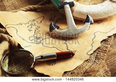 Lifebuoy with magnifier and anchor on old map. Happy Columbus day concept