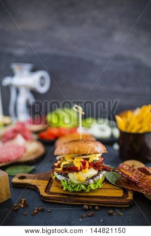 Tasty street food grilled beef burger in crispy shortbread with lettuce and mayonnaise served on small cutting board a rustic wooden table with ingredients and meat grinder in background.