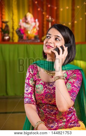 indian attractive girl talking over cel phone or mobile phone or smartphone in ganpati festival or ganesh utsav