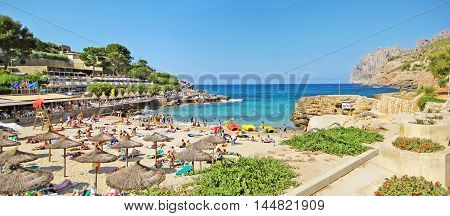 Cala Sant Vicenc Majorca Spain - June 28 2008: Beach panorama of Cala Molins famous bay in the north of Majorca. Resting tourists / people under typical majorcan sunshades