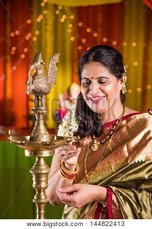 Indian woman in traditional saree lighting oil lamp or samai with diya and celebrating ganesh festival or Diwali or deepavali. Indian lady holding oil lamp indoors.