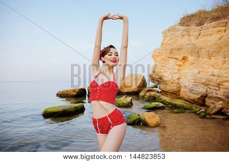 Young beautiful pin up girl in red swimsuit posing with her hands up while standing at the beach