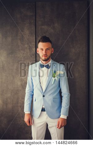 Fiance wearing blue suit and white pants with a bow tie