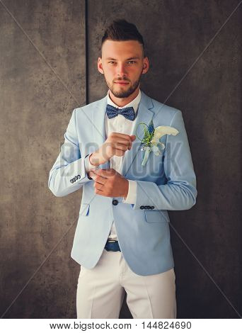 handsome fiance wearing blue suit and white shirt with a bow tie